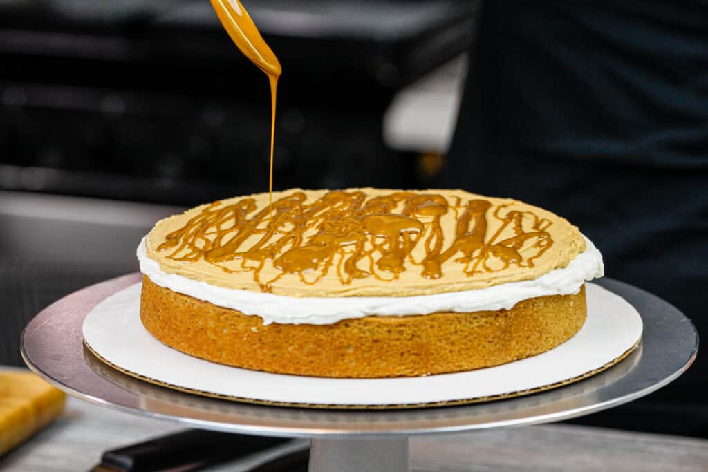 image of cookie butter cake being assembled and drizzled with cookie butter between each cake layer
