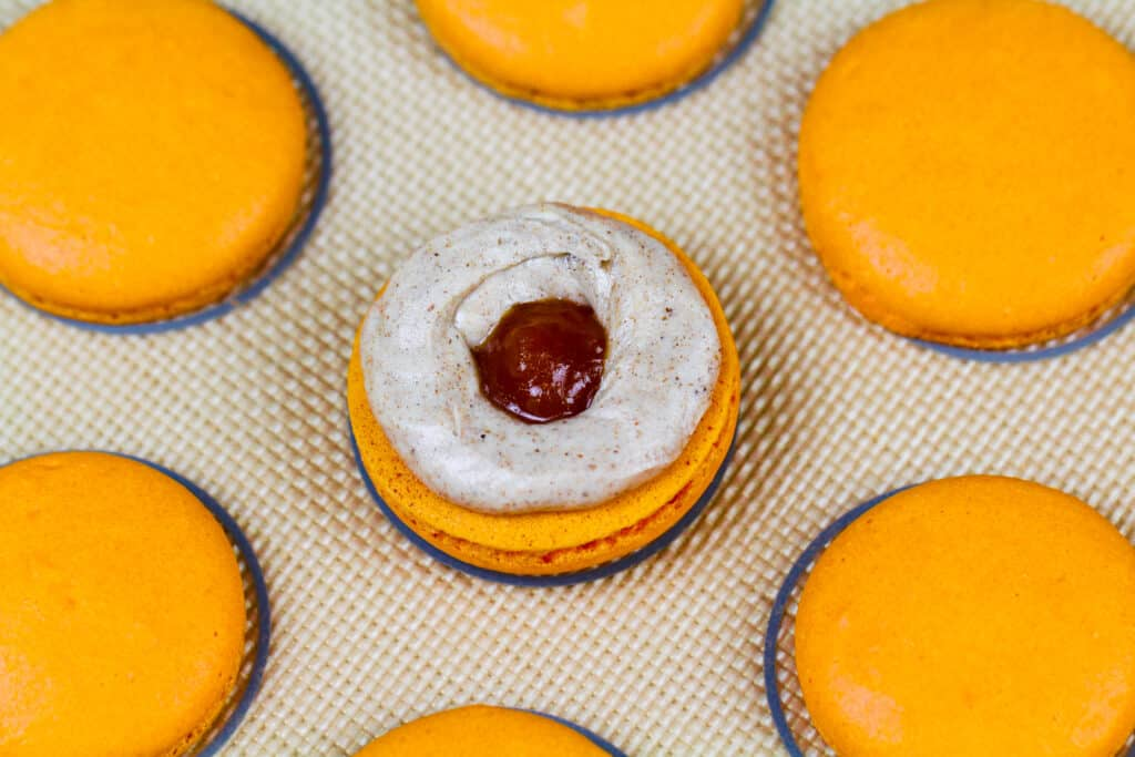 image of a pumpkin macaron being filled with spiced buttercream and pumpkin pie filling