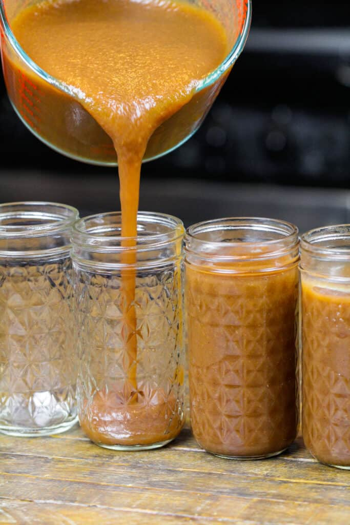 image of instant pot apple butter being poured into mason jars