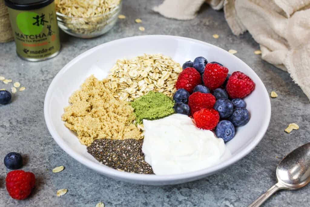 image of ingredients in a bowl to make overnight oats with chia seeds, greek yogurt, brown sugar, berries, honey and old fashioned oats