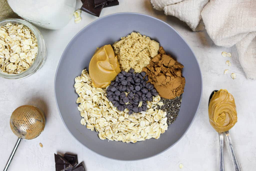image of ingredients in a bowl to make chocolate peanut butter overnight oats