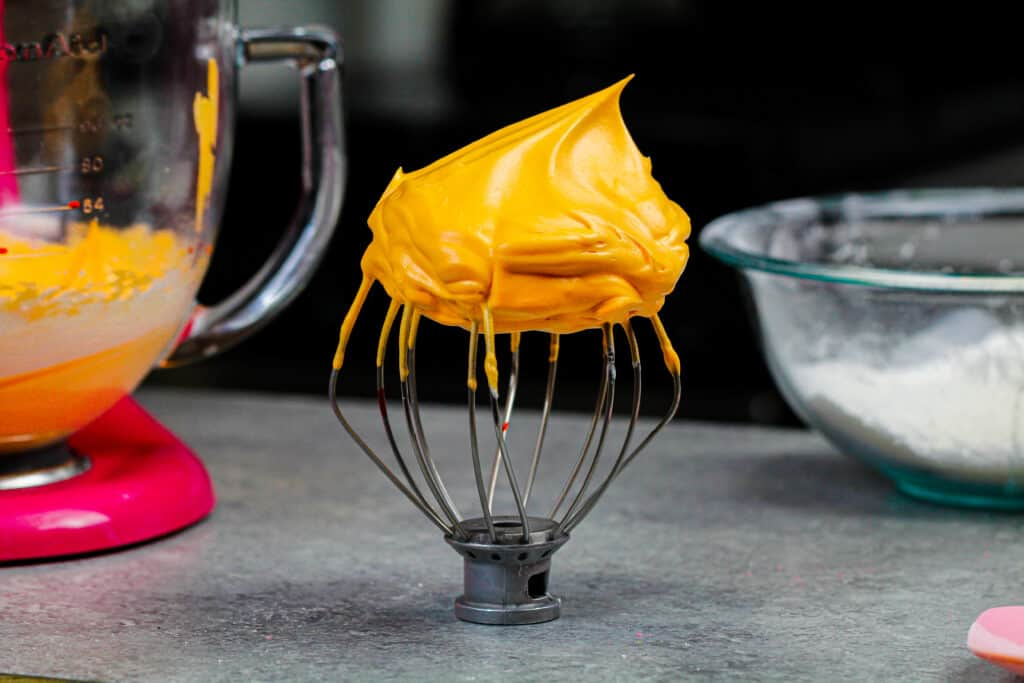 image of orange meringue on a whisk ready to be made into pumpkin macarons