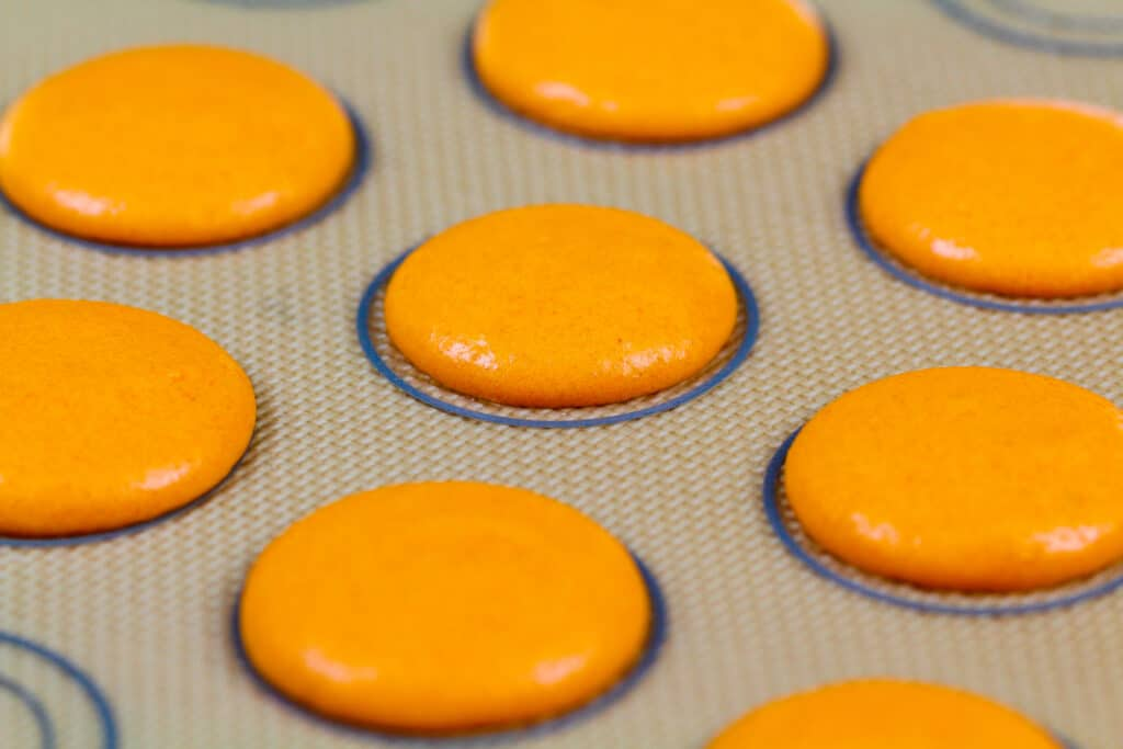 image of orange french macaron batter being piped onto a silpat mat to make pumpkin macarons