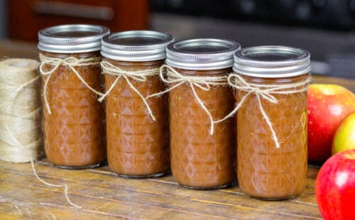 image of instant pot apple butter poured into tall mason jars before being frozen