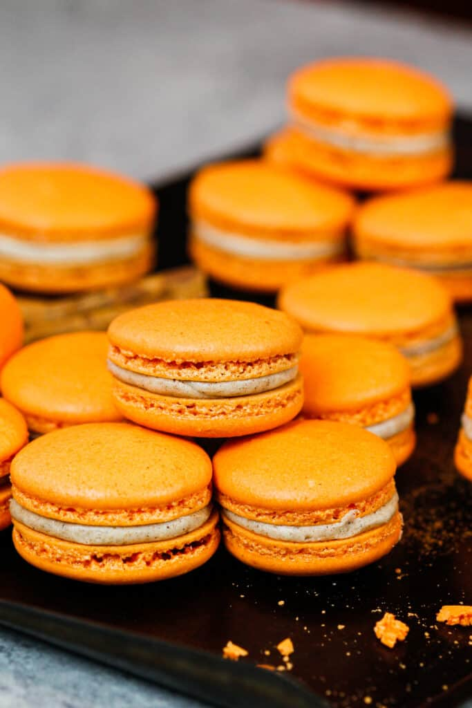 image of pumpkin macarons on a baking tray