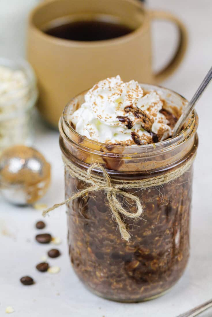 image of coffee overnight oats topped with whipped cream and chocolate syrup
