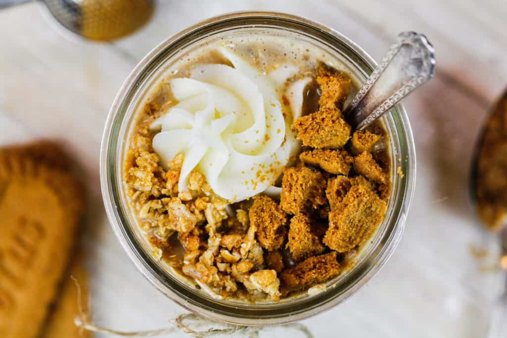 image of a mason jar overhead filled with cookie butter overnight oats and topped with whipped cream, chopped up biscoff cookies and some granola