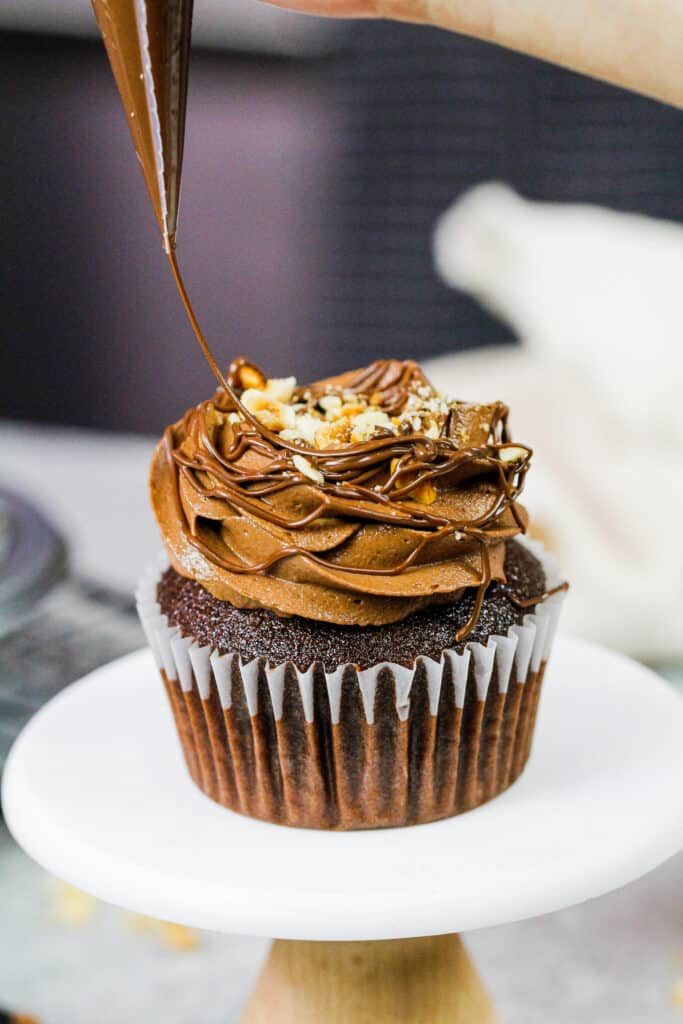 image of a Nutella cupcake being drizzled with additional Nutella to decorate it
