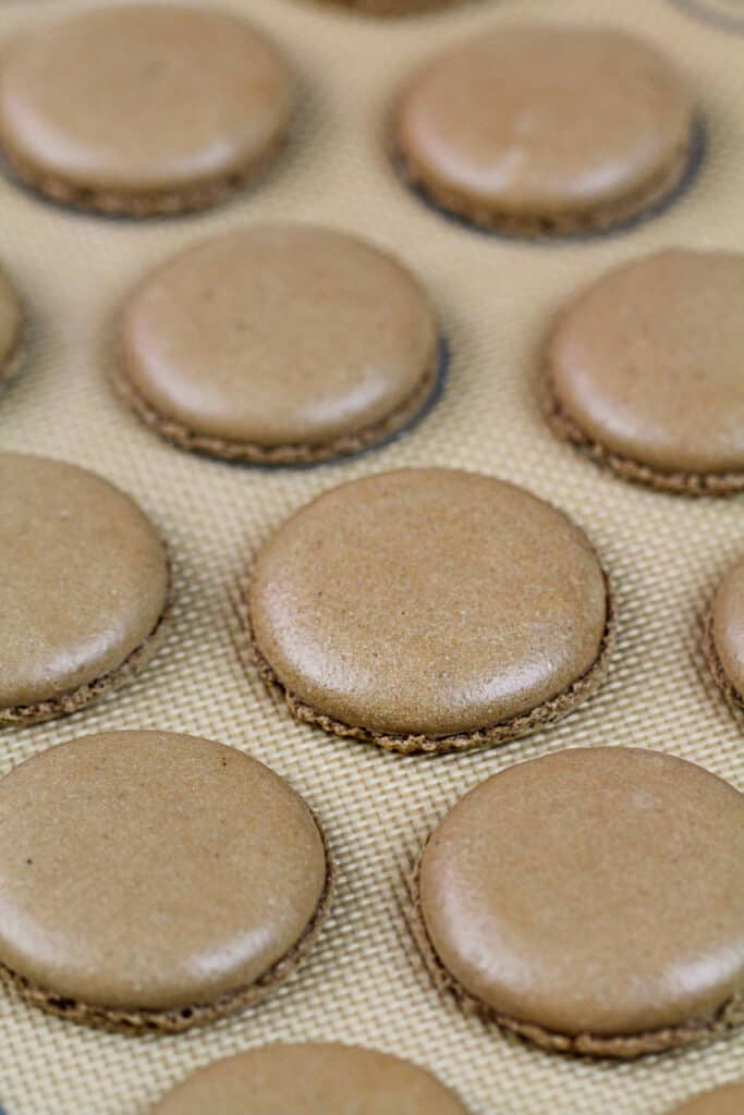image of chocolate macaron shells baked on a silpat mat and cooling