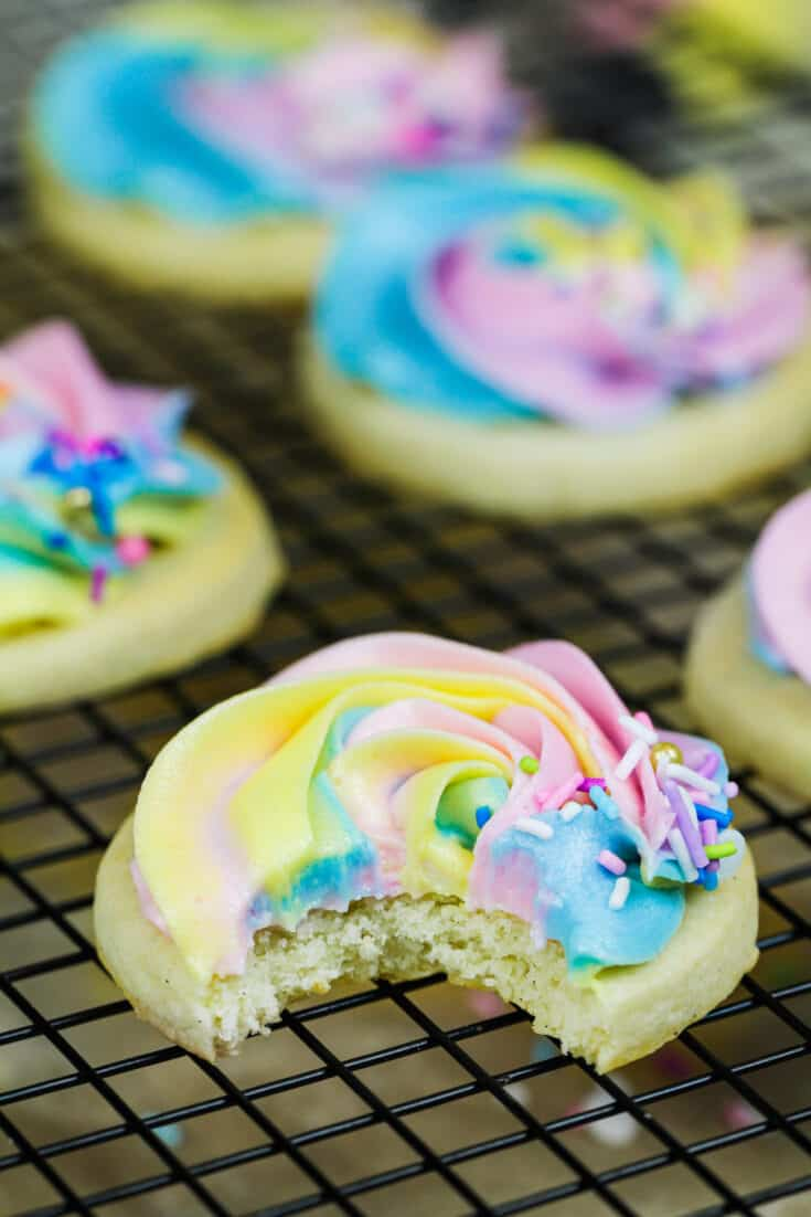 image of buttercream cookies that have been frosted with pretty pastel frosting and bitten into to show how soft and chewy the cookies are