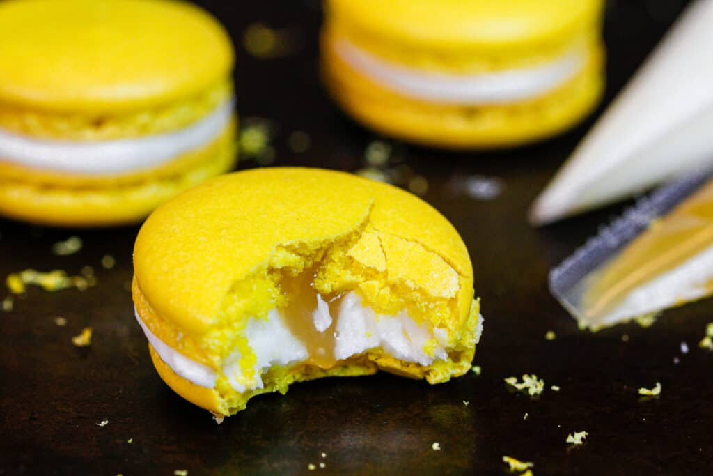 image of a lemon macaron that's been bitten into to show its lemon curd filling and fresh lemon buttercream