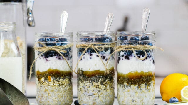 image of blueberry overnight oats filled in mason jars before being stirred with milk