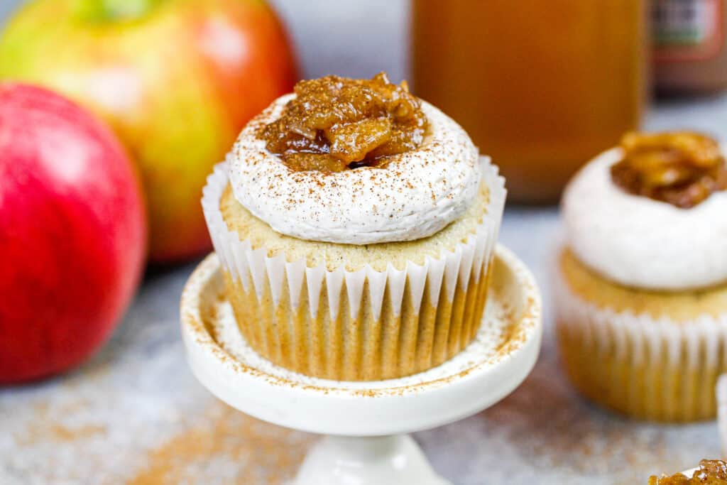 image of an apple cider cupcake on a cupcake stand after being decorated