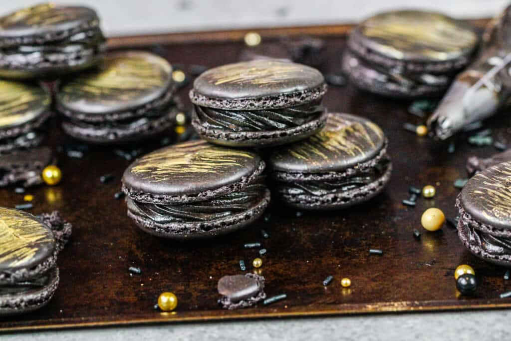 image of french black macarons that have been filled with black frosting and brushed with a beautiful gold streak of edible gold paint