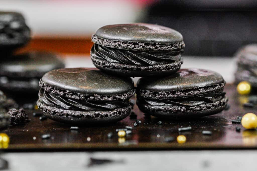 image of black macarons stacked on a baking tray to show their black chocolate frosting