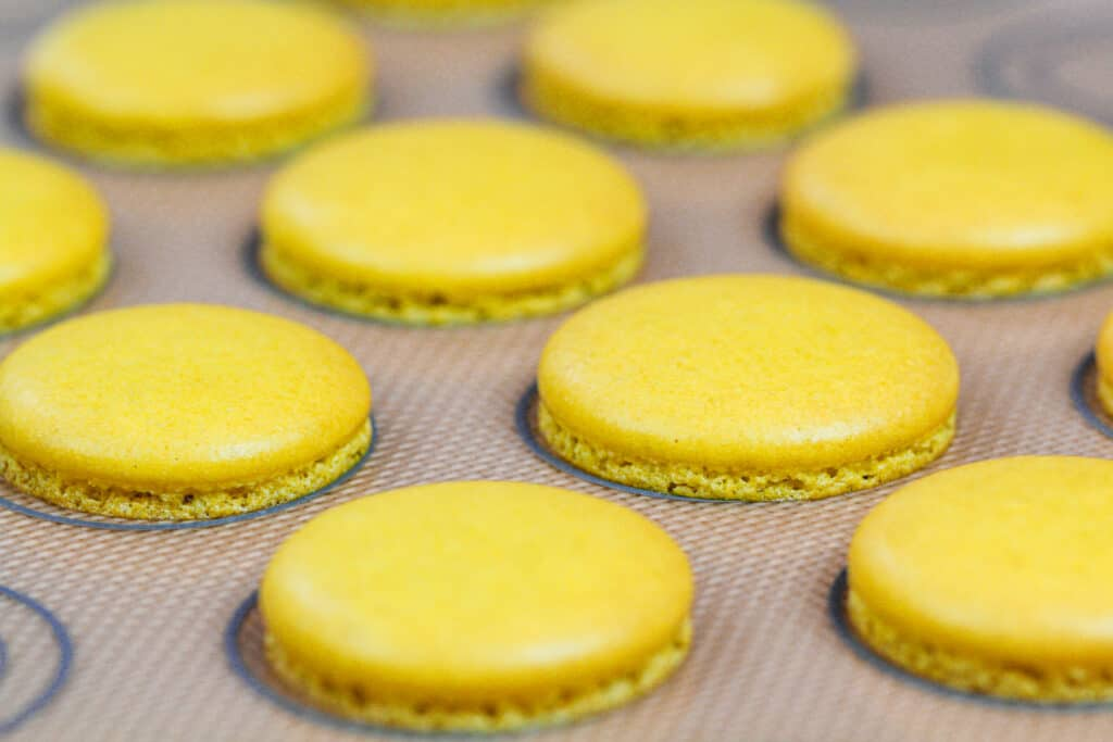 image of perfectly baked yellow macaron shells with feet and no browning