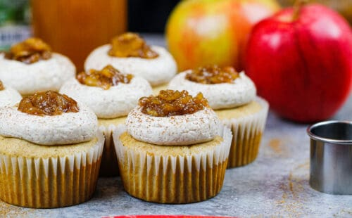 image of apple cider cupcakes topped with apple pie filling and a dusting of cinnamon