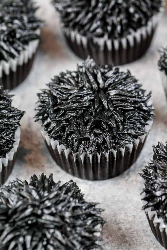 image of cupcakes frosted with black frosting using a grass tip to make soot sprite cupcakes