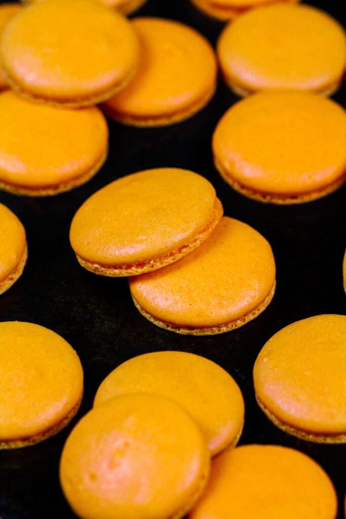 image of orange macaron shells that have been baked to make pumpkin macarons