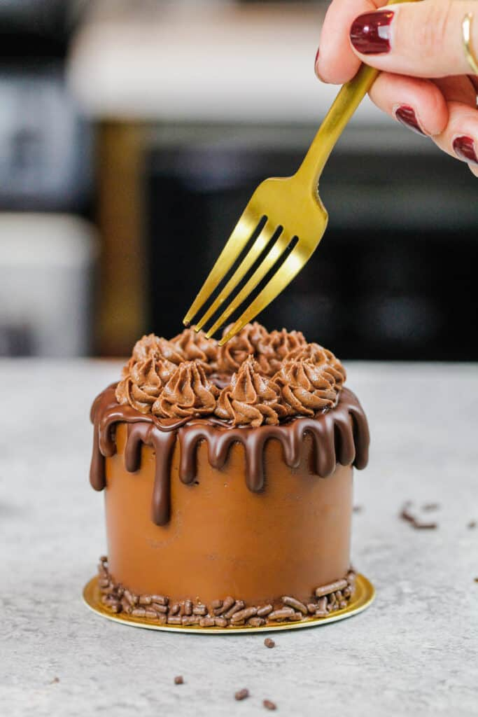 image of a mini chocolate cake that's about the cut into with a fork to show how small it is