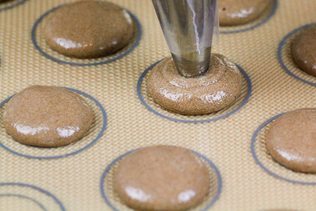 image of chocolate macarons being piped onto a silpat mat