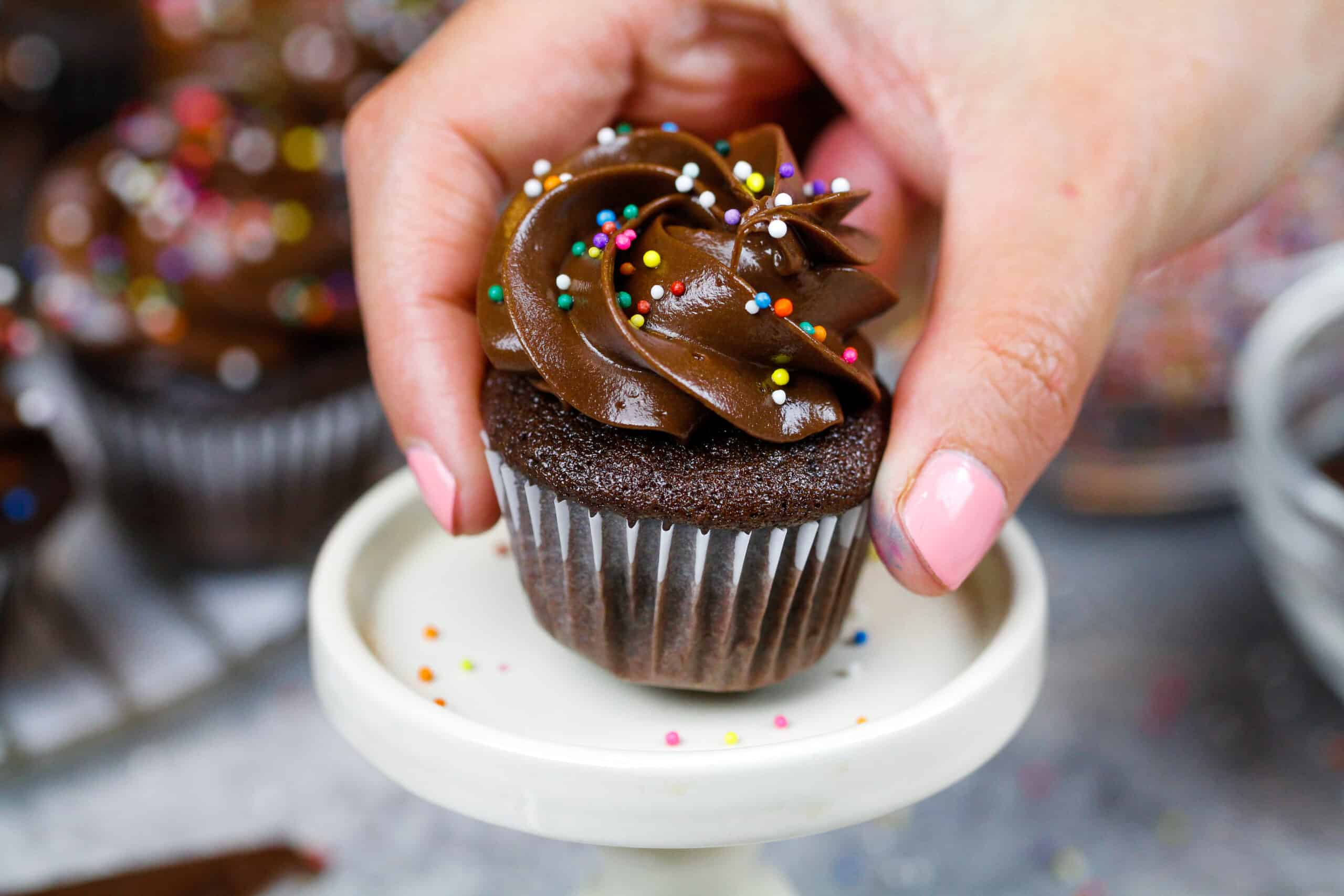 image of a mini chocolate cupcake being placed on a mini cake stand