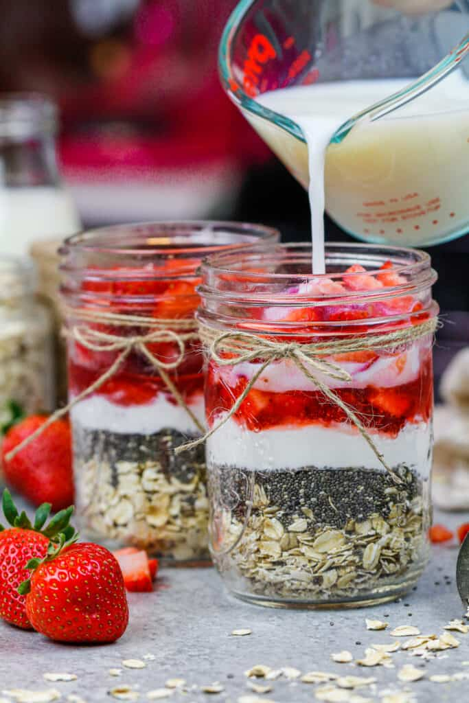 image of milk being poured into a mason jar filled with ingredients to make strawberry overnight oats