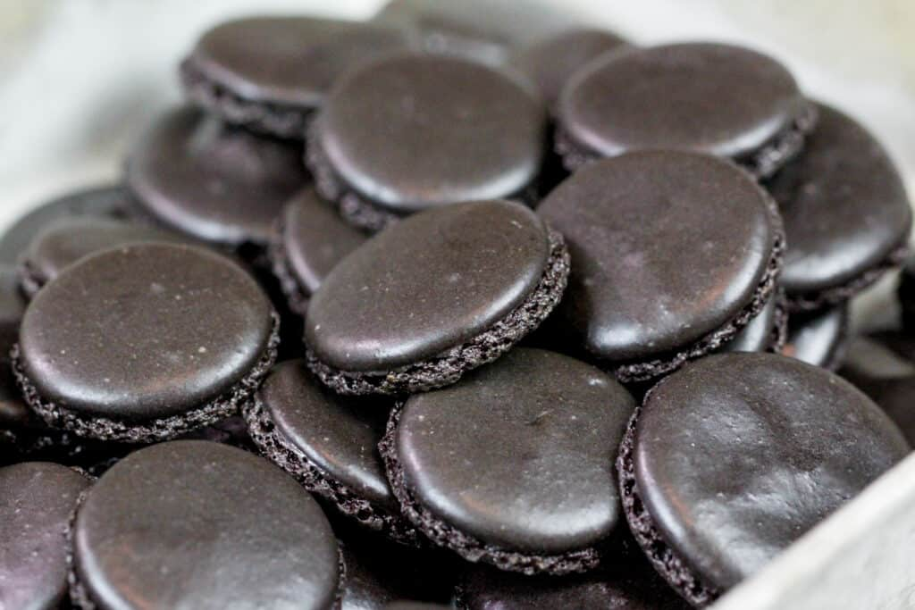image of black macaron shells that have been baked and cooled and are ready to be filled