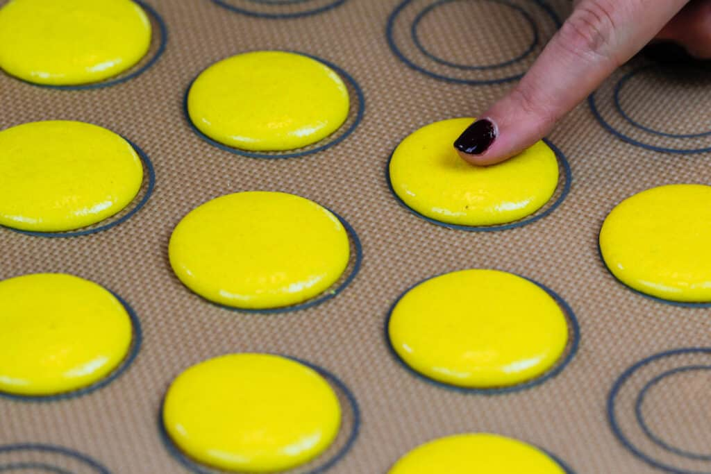 image of yellow macaron shells that have rested and have formed a touchable skin before being baked