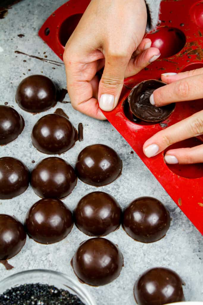 image of chocolate shells being removed from a silicone mold to make a hot chocolate bombs recipe