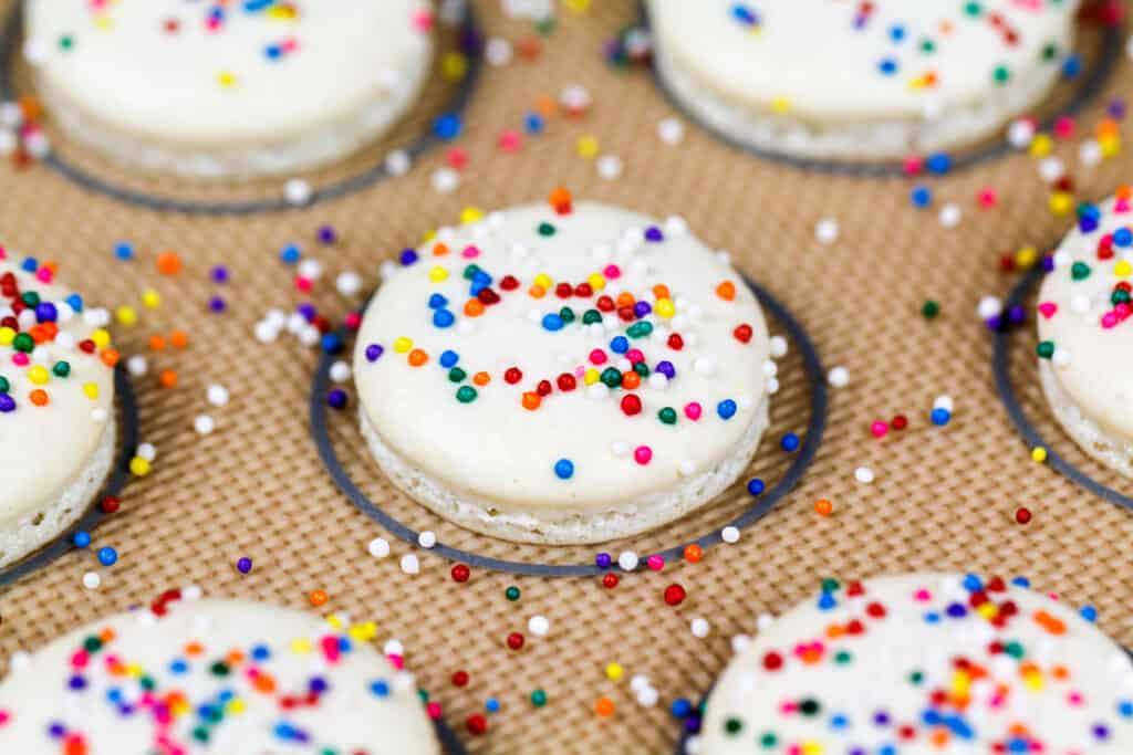 image of baked white macaron shells topped with nonpareil sprinkles to make rainbow macarons