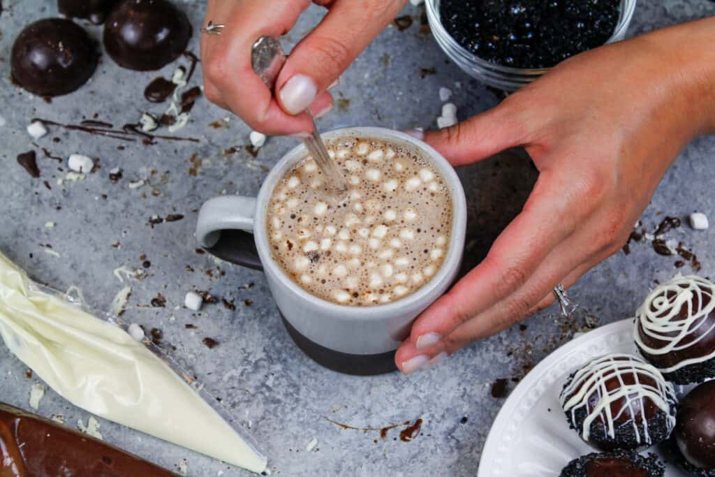 image of a mug of hot cocoa that was made with a hot chocolate bomb filled with mini marshmallows