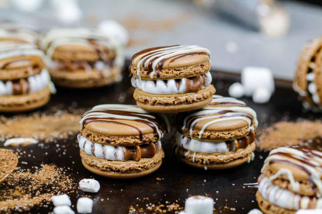 image of hot cocoa macarons filled with hot cocoa and marshmallow buttercream that are stacked a tray surrounded be mini marshmallows
