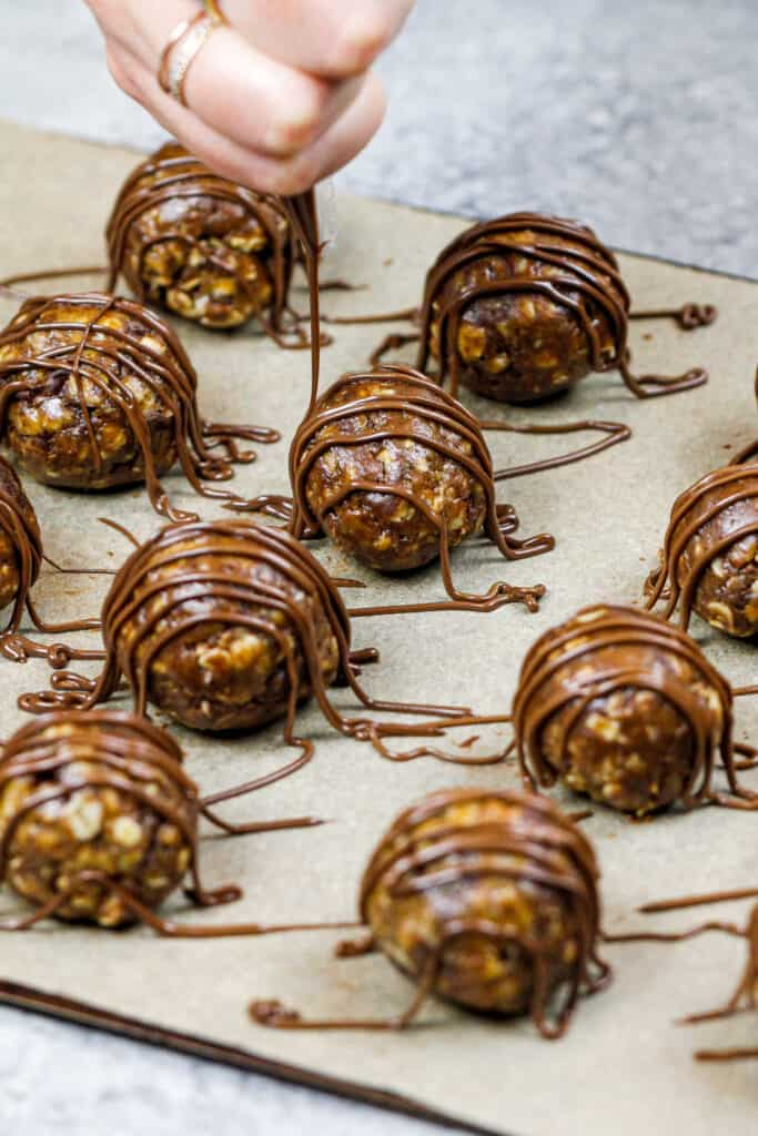 image of oatmeal peanut butter balls being drizzled with melted chocolate