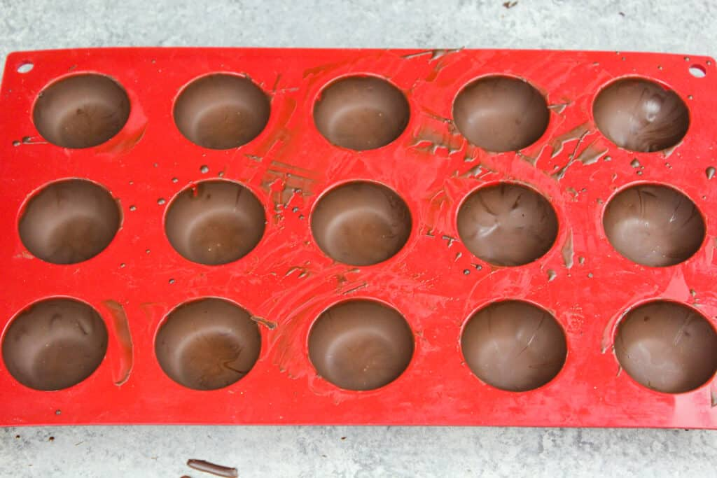 image of a small silicone mold being used to make mini hot chocolate bombs