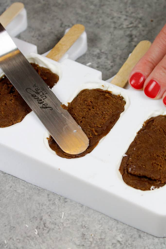 image of a silicone mold being filled with cake to make cakesicles or cake popsicles