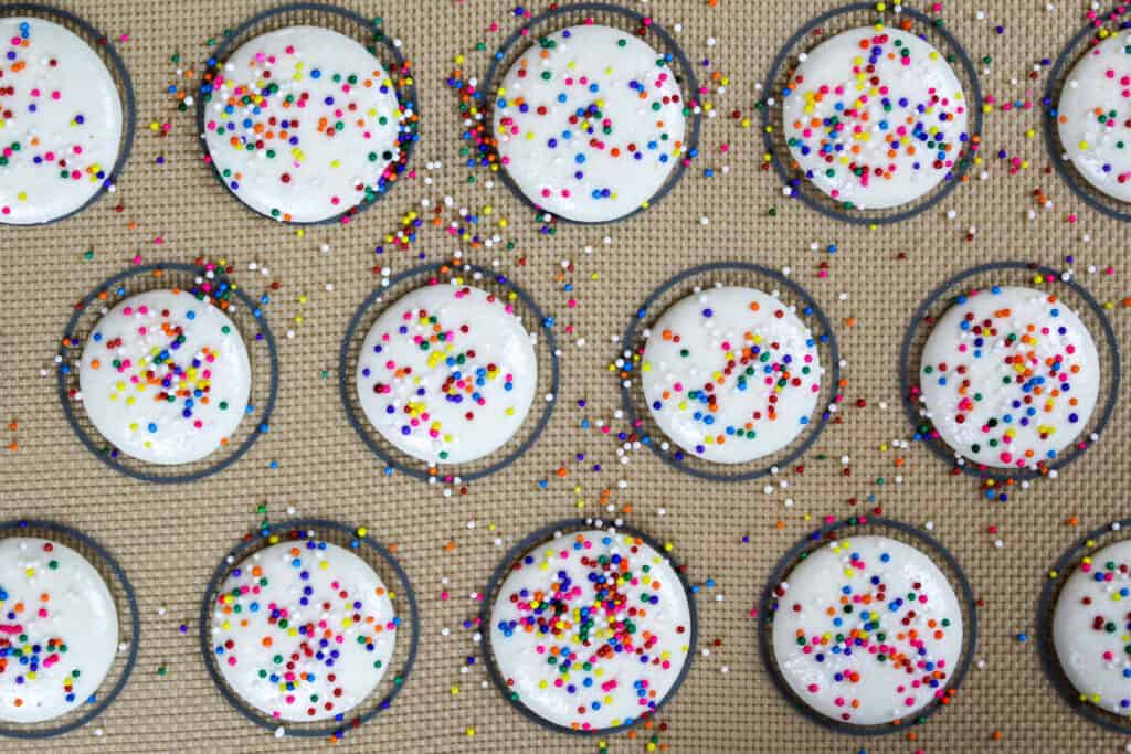 image of white macaron shells topped with rainbow sprinkles being rested before being baked