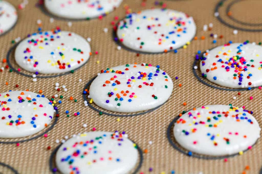 image of white macaron shells topped with rainbow sprinkles that have rested and are ready to be baked