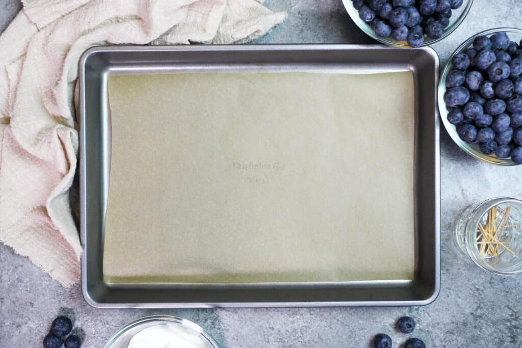 image of a lined baking sheet prepared to make frozen yogurt blueberries