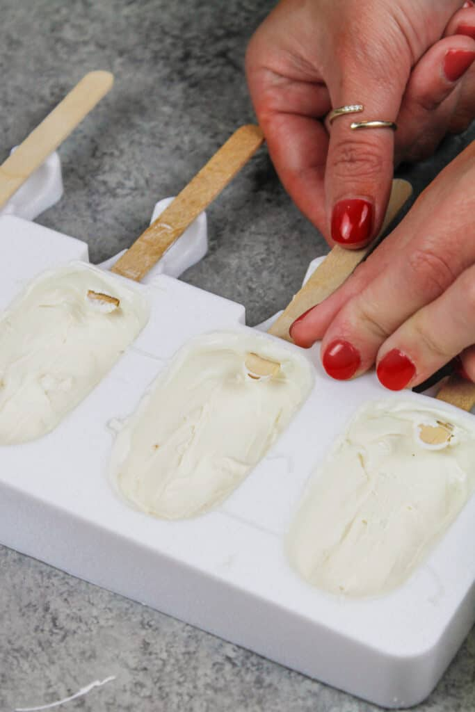 image of white chocolate and candy melts being painted into a silicone mold to make cakesicles, while inserting a popsicle stick to keep the opening in the mold open for later