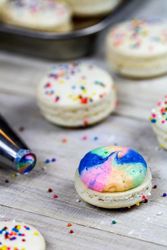 image of a rainbow macaron with rainbow buttercream ready to be topped with it's second macaron shell