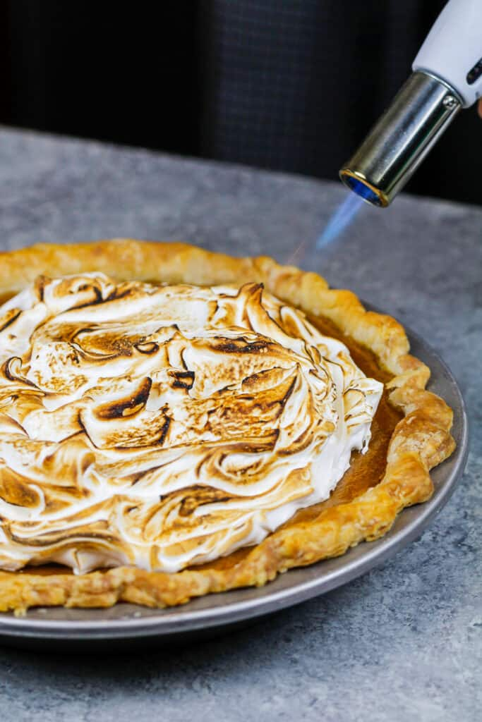 image of meringue being toasted on a mascarpone pumpkin pie