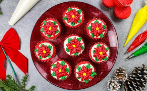image of poinsettia cupcakes placed on a festive red cake stand