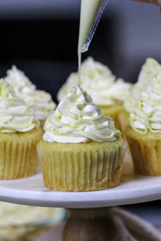 image of white chocolate cupcakes that have been filled with white chocolate ganache and frosted with a fluffy white chocolate buttercream then drizzle with melted white chocolate