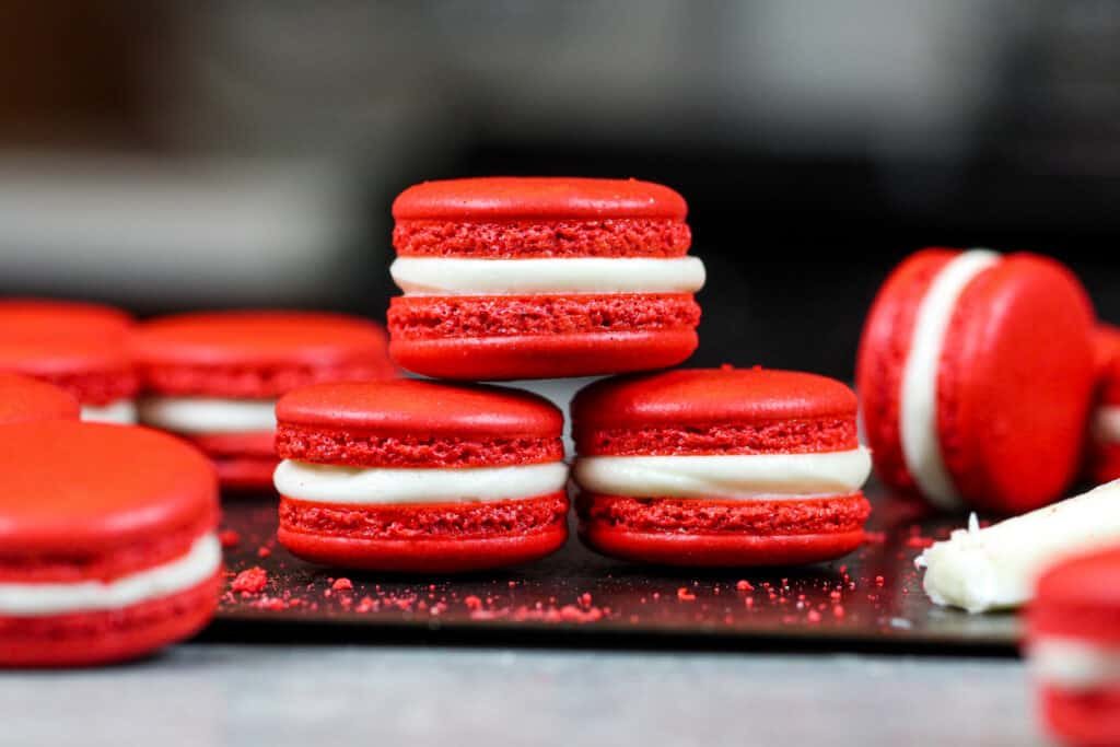 image of red velvet macarons filled with cream cheese frosting that are stacked on each other to show their perfect feet