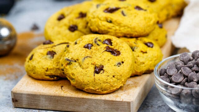 image of vegan pumpkin chocolate chip cookies stacked on a board ready to be eaten