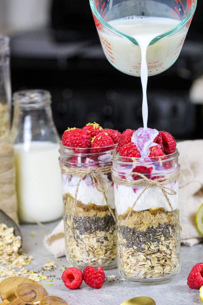 image of milk being poured into a mason jar to make raspberry overnight oats