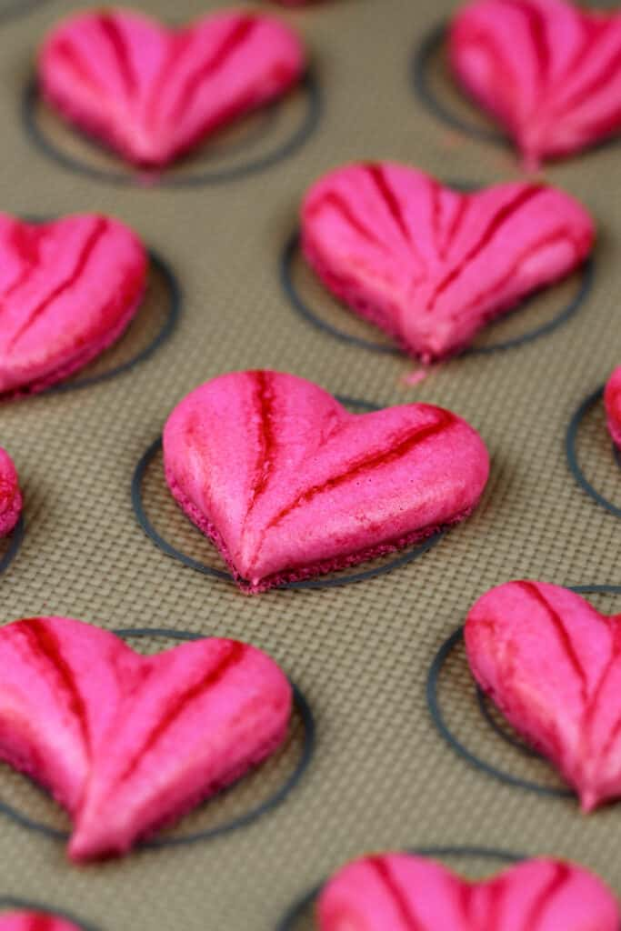 image of pretty pink heart shaped macarons that have been baked are are ready to be filled