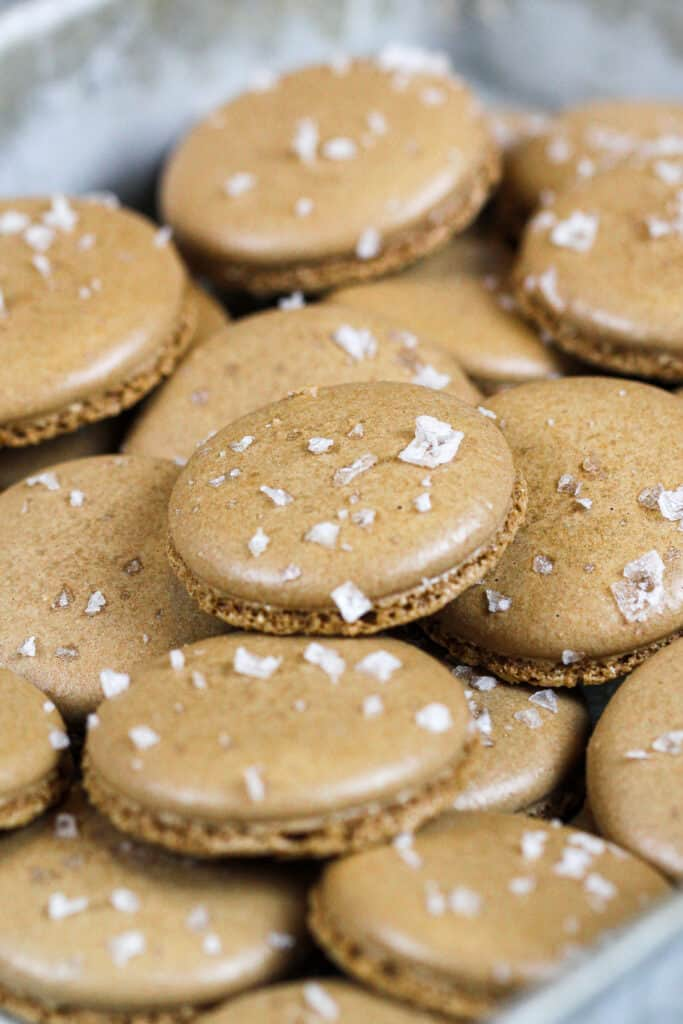image of chocolate macaron shells that have been sprinkled with sea salt to make salted caramel macarons