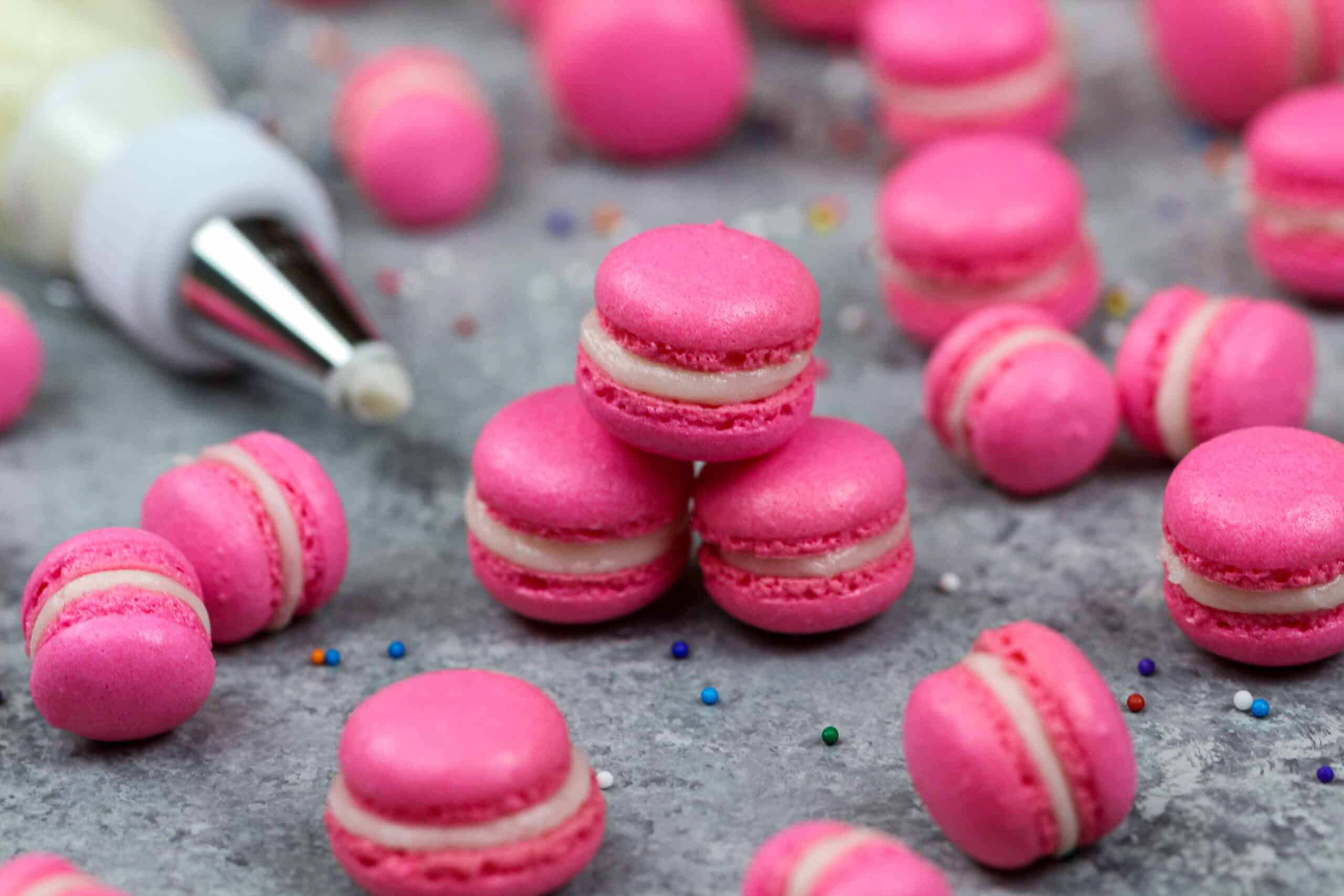 image of mini macarons colored pink with gel food coloring and filled with american buttercream